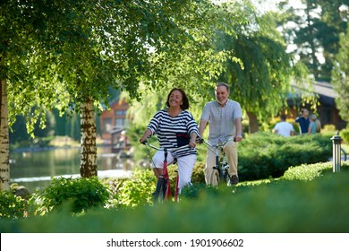 Happy senior couple cycling in the park. Outdoor bike ride.