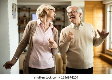 Happy senior couple dancing and having fun at home.