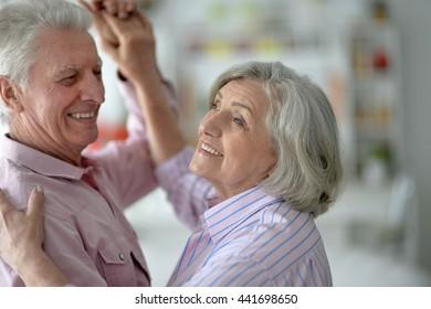 happy senior couple dancing at home