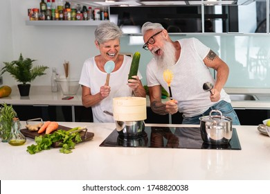 Happy senior couple dancing while cooking together at home - Mature people having fun preparing the lunch - Joyful elderly lifestyle and food nutrition concept - Main focus on man face
