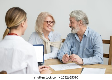 Happy senior couple deciding discussing new house purchase at meeting with agent, smiling older aged family consulting about buying home, taking mortgage loan, making investment or real estate deal