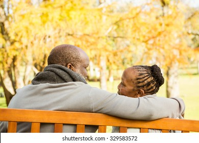 Happy senior couple discussing together on a bench in parkland