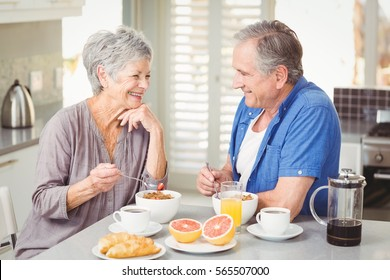 Happy senior couple discussing while having breakfast at table