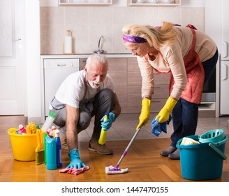 Happy senior couple doing chores together on floor