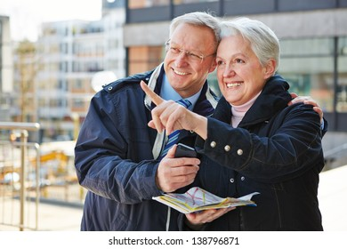 Happy senior couple doing sightseeing tour on city trip with a map