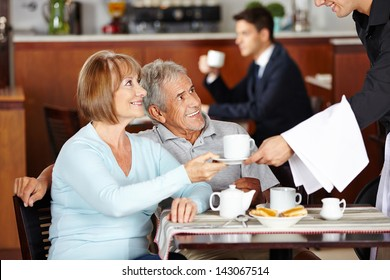 Happy senior couple drinking coffee at coffee shop in hotel