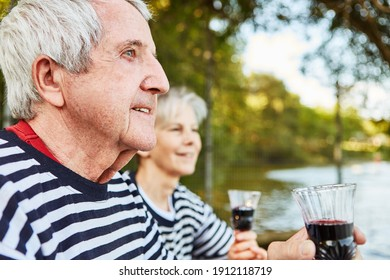 Happy senior couple drinking wine in nature by the lake on weekend