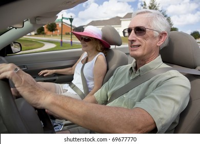 A happy senior couple driving a convertible car wearing sunglasses
