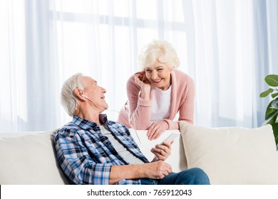 happy senior couple in earphones listening music together at home