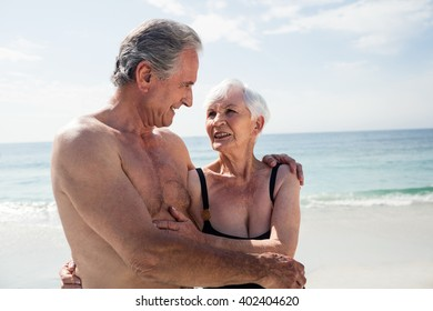Happy senior couple embracing on the beach on a sunny day