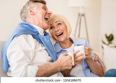 Happy senior couple enjoying tea and laughing, having conversation on sofa at home