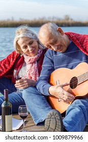 Happy senior couple enjoying time together playing guitar and drinking wine by the lake wrap around in a red blanket.