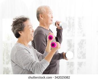 happy senior couple exercising with dumbbells