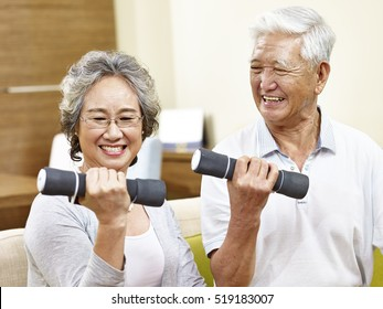 happy senior couple exercising using dumbbells, happy and smiling