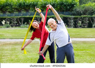 Happy Senior Couple Exercising With Yoga Belt In Park
