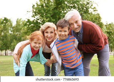 Happy senior couple with grandchildren in park