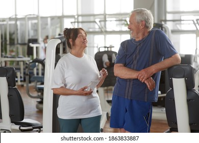Happy senior couple at gym. Elderly people resting at fitness center. Peple, sport, leisure, healthy lifestyle concept.