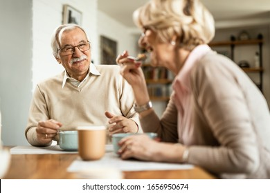 Happy senior couple having a breakfast together in the morning. Focus is on man.