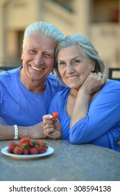 Happy Senior couple having breakfast in cafe with strawberries