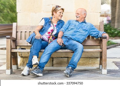 Happy senior couple having fun on a bench - Concept of active playful elderly during retirement - Everyday lifestyle in autumn sunny afternoon - Soft vintage filtered look with slightly blurred edges