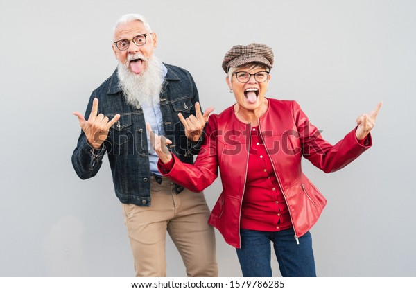 Happy senior couple having fun together outdoor - Retired man and woman celebrating crazy moments - Elderly people lifestyle and love relationship concept