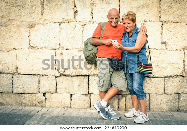 Happy senior couple having fun with a modern smartphone - Concept of active elderly and interaction with new technologies - Travel lifestyle without age limitation - Warm vivid filter