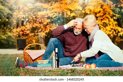 happy senior couple having a picnic at the autumn forest