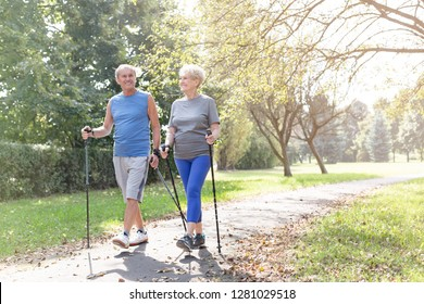 Happy senior couple with hiking poles walking in park