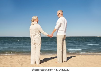 happy senior couple holding hands summer beach