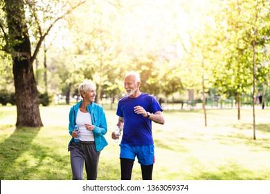 Happy senior couple jogging outdoors in park.