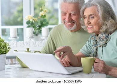 happy senior couple with laptop