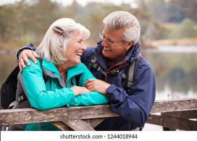 Happy senior couple leaning on a wooden fence smiling to each other, close up, Lake District, UK