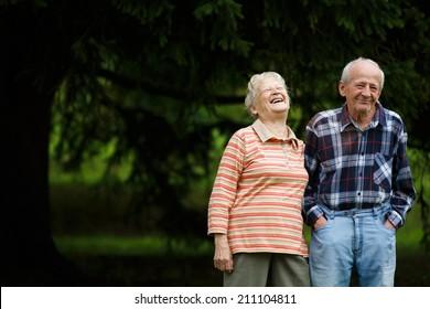 Happy Senioren, die Kamera anschauen und lachen, Senior Frau umarmt ihren Partner an einem sonnigen Tag, Lächeln kaukasisches älteres Paar umarmt