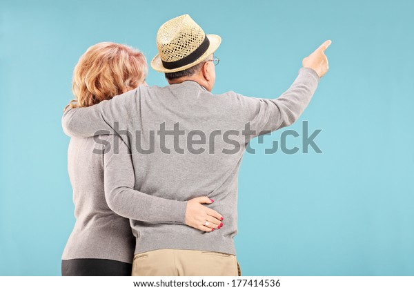 Happy senior couple looking at something isolated on blue background, rear view