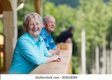 Fröhliches Seniorenpaar mit Blick auf die Umgebung und Lächeln. Schauen Sie in einem Holzturm und beobachten Sie die Naturlandschaft im Wald. Sommerferien. unscharfer Waldhintergrund.
