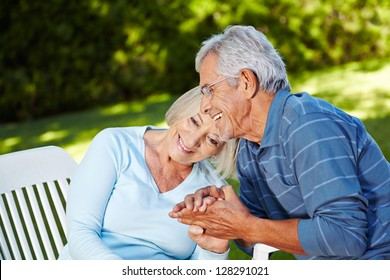 Happy senior couple in love sitting outside in a garden
