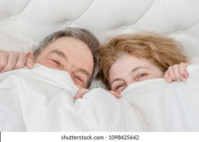 Happy senior couple lying under the blanket together. Top view