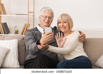 Happy Senior Couple Making Video Call On Phone And Waving To Caller