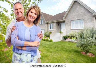 Happy senior couple near new house.
