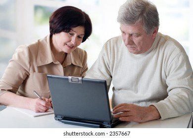 """Happy senior couple on laptop. Concept may be is """"home office"""" or """"shopping in internet shop""""."""