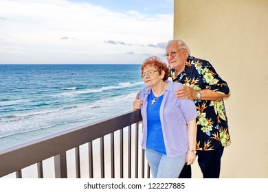 A happy senior couple on vacation gaze out at the Atlantic Ocean from their balcony over Port Canaveral Beach in Florida, enjoying the scene.