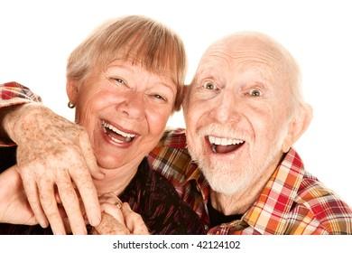 Happy senior couple on white background laughing broadly