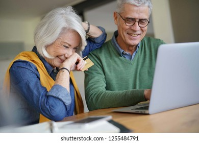 Happy senior couple online shopping at home