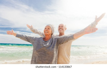 happy senior couple with outstretched arms enjoying retirement