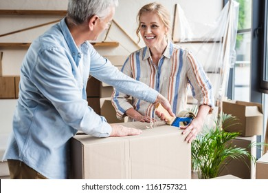 happy senior couple packing cardboard box and smiling each other during relocation