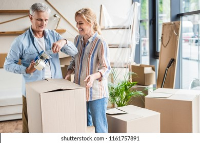 happy senior couple packing cardboard boxes during relocation