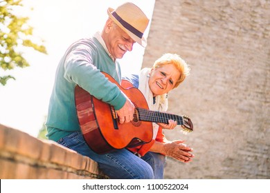 Happy senior couple playing a guitar and having a romantic date outdoor - Mature people having fun enjoying time together in vacation - Concept of elderly lifestyle activities