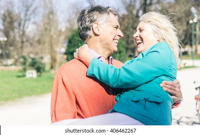 Happy senior couple playing in the park and sharing good feelings