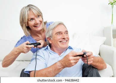 Happy senior couple playing video games at home with controller