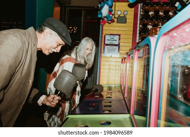 Happy senior couple playing whack a mole at a game arcade